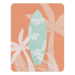 A coral nursery rug with with a pale blue surfboard with silhouettes of hibiscus on it.  The rug also has silhouettes of palm trees around it. This rug is perfect for your beach themed nursery or for your kids playroom.