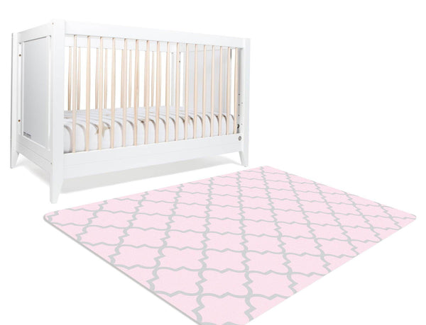 A geometric nursery rug with moroccan trellis design. The gray trellis design is on a pink background on a rectangular rug. This nursery rug is perfect for your daughter's princess themed nursery.