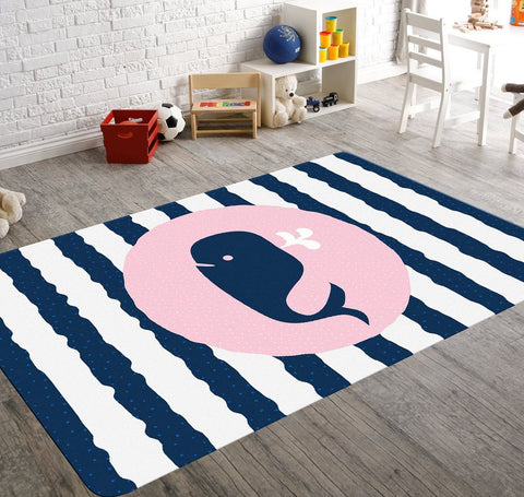 A nautical nursery rug with navy and white wavy stripes. This rectangular rug has a baby whale in the center on a pink circular background.