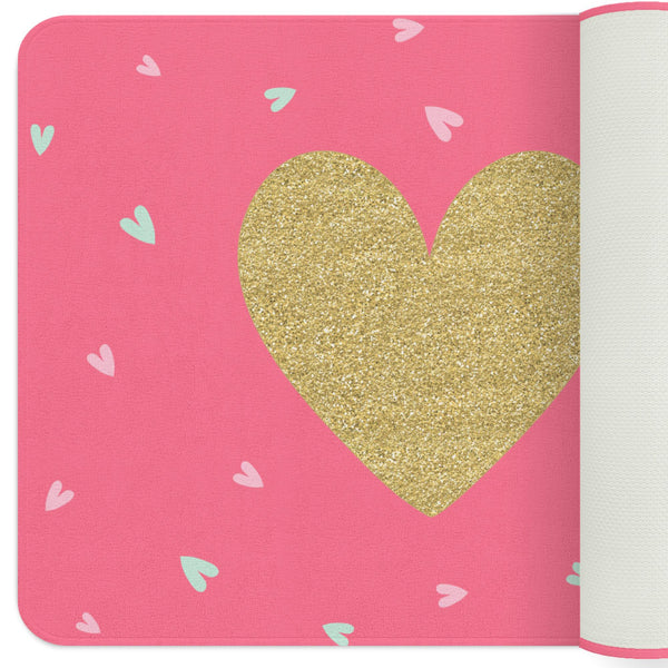 A pink nursery rug for your baby girl with a golden heart in the center. The rug also has pale pink and mint hearts all over it.