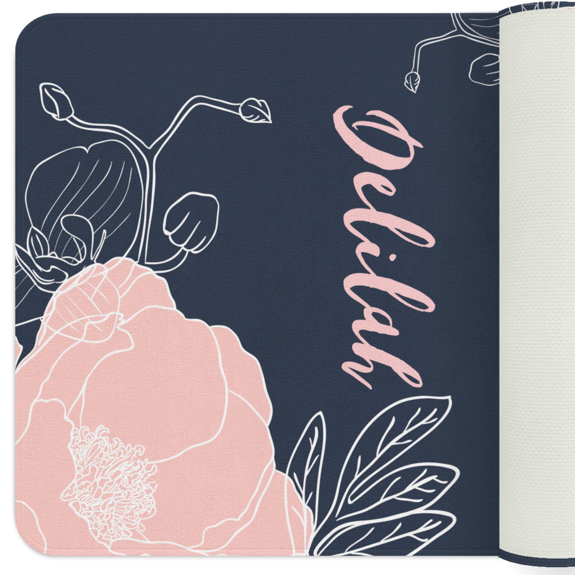 A navy floral rug with a blush flower illustration on diagonally opposite corners. The nursery rug also has a customized monogram in the center.