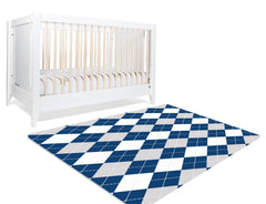 A rectangular rug with argyle pattern. This geometric pattern consists of diamond shapes in navy, white and gray. This argyle patterned rug will go with any nursery theme and will give your baby girl's nursery a sophisticated look.