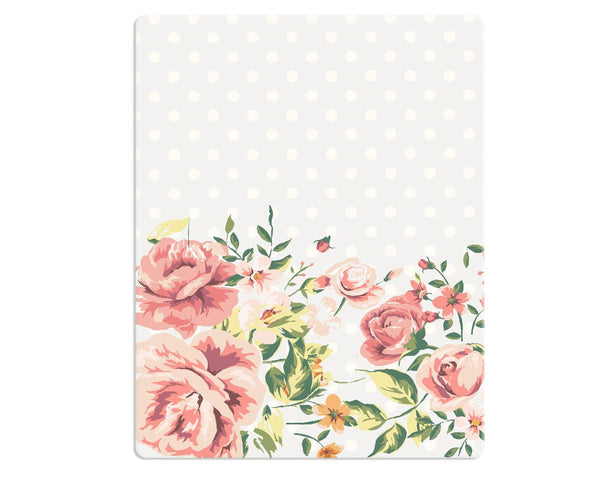 A floral rug with beautiful pink flowers and leaves on one side of the rug which beautifully stand out on a background which is subtle gray with white polka dots.