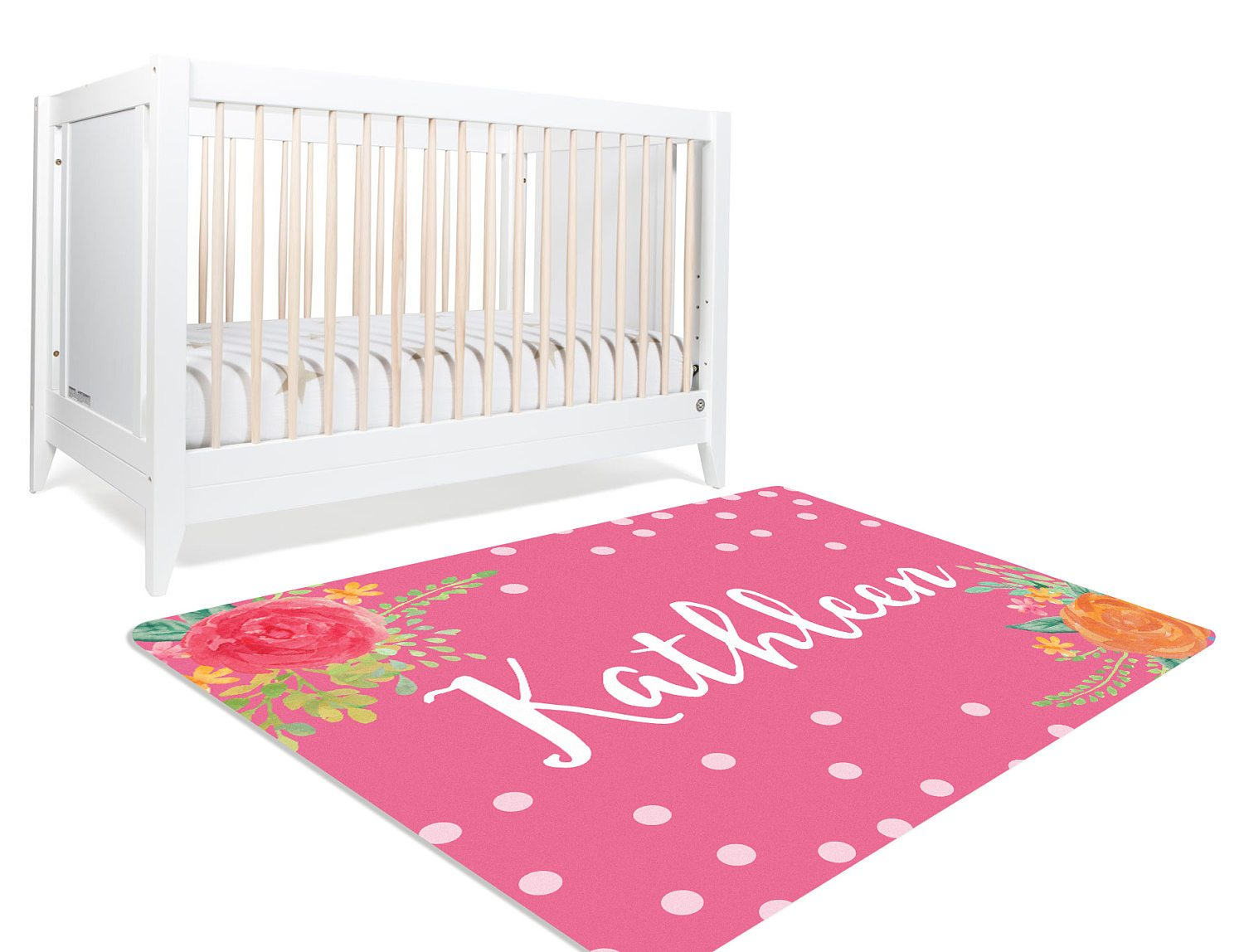 A pink floral nursery rug with white polka dots strewn around and a bunch of flowers on two diagonally opposite corners of the rug. It is customized to the name of your child. Perfect for a floral themed nursery.