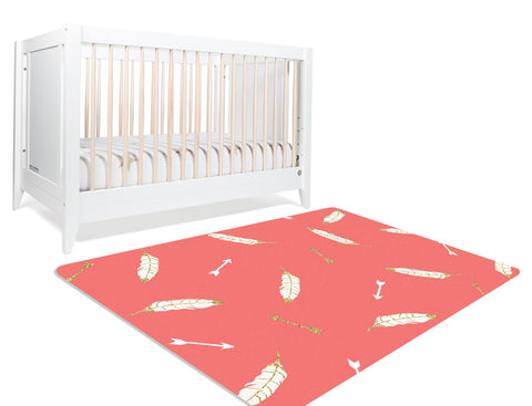 A rectangular coral rug with gilded arrows and gilded white feathers strewn across the rug makes it perfect for your mountain themed nursery or your girl's playroom.