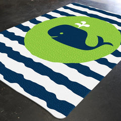 A nautical nursery rug with navy and white wavy stripes. This rectangular rug has a baby whale in the center on a green circular background.