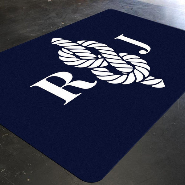 A nautical nursery rug with a white colored sailor knot in the center. There are two letters in white on either side of the sailor knot which can be personalized.