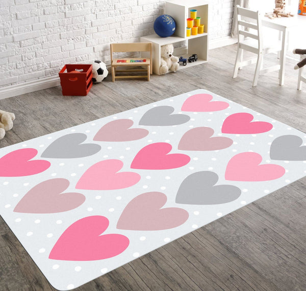 A nursery rug with three rows of colorful hearts. The hearts are placed on a pale blue background and cute white polka dots.