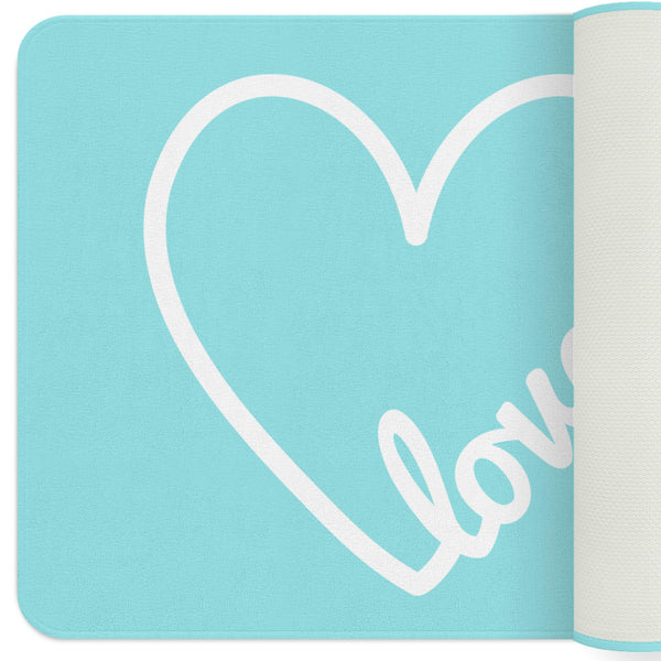 A turquoise nursery rug with a white heart at the center with love typography on the heart.