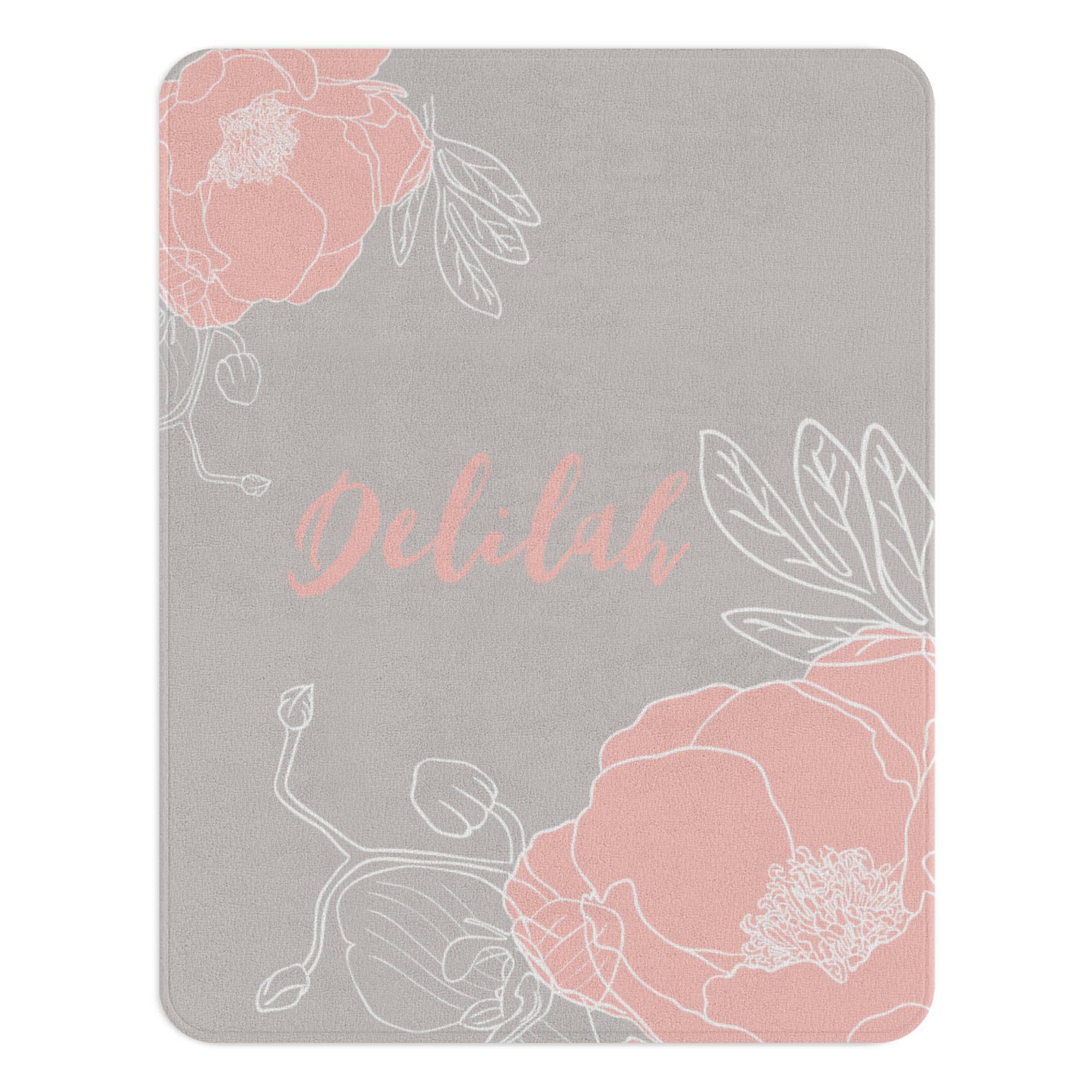 A gray floral rug with a blush flower illustration on diagonally opposite corners. The nursery rug also has a customized monogram in the center.