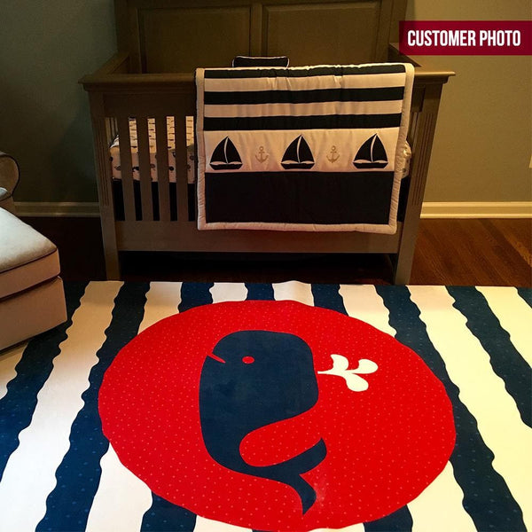 A nautical nursery rug with navy and white wavy stripes. This rectangular rug has a baby whale in the center on a red circular background.