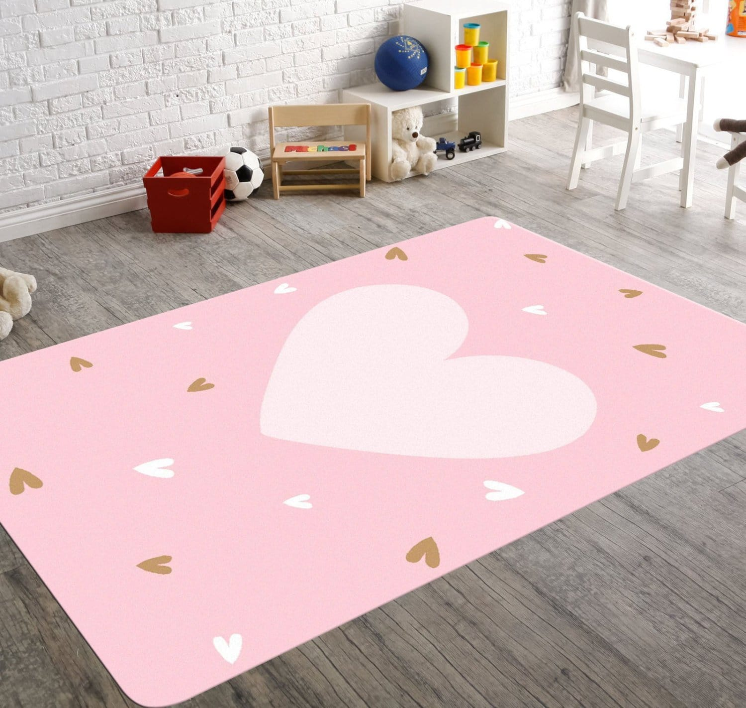 A pink nursery rug for your little girl with a big pale heart in the center. The rug also has small pale pink and gold hearts sprinkled all over the rug.