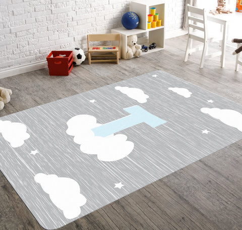 A custom cloud rug for your boy with his initial in pale blue perched on a cloud in a night sky. This gray rug  along with a sprinkle of stars is a safe choice for your baby boy's nursery or his playroom.