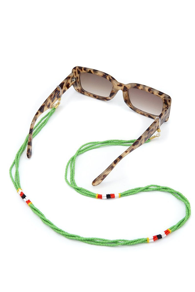 Kijani Sunnycord handmade in Kenya with green glass beads, attached to sunglasses.