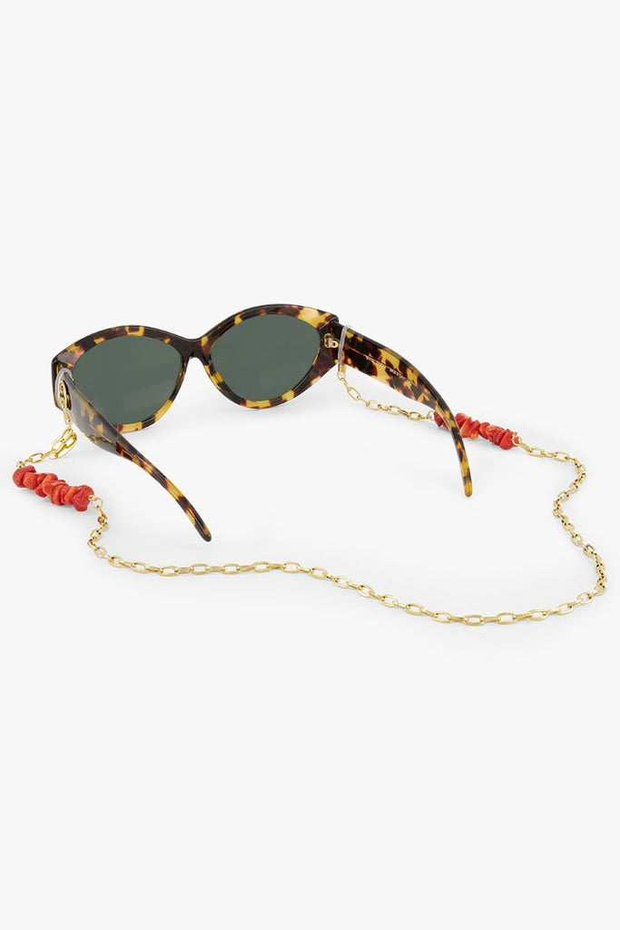 Coral Lola Sunnycord made of 18K gold-plated chain and red coral chips, attached to brown sunglasses.