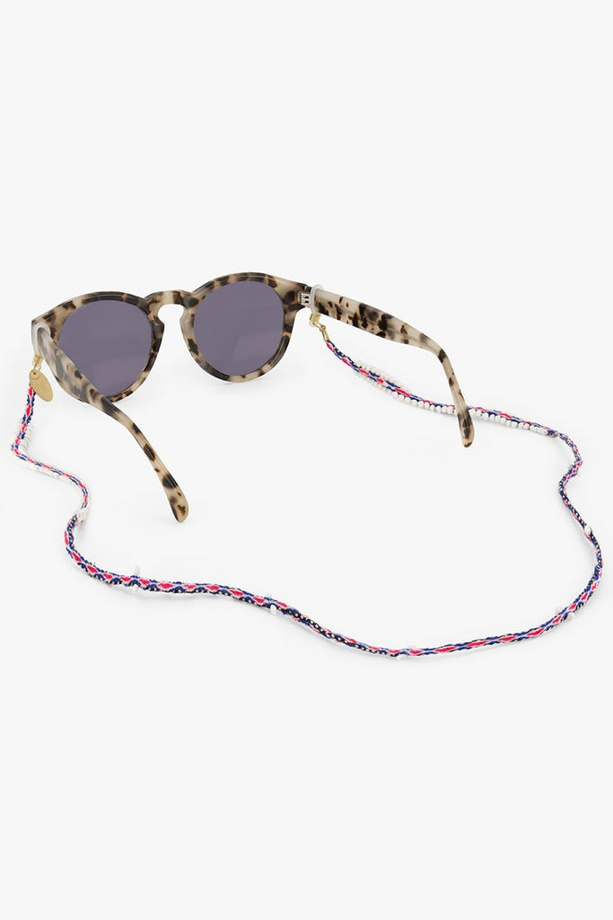 Maya Sunnycord handmade in Peru, made of blue, pink and white woven colours and glass beads, attached to sunglasses.