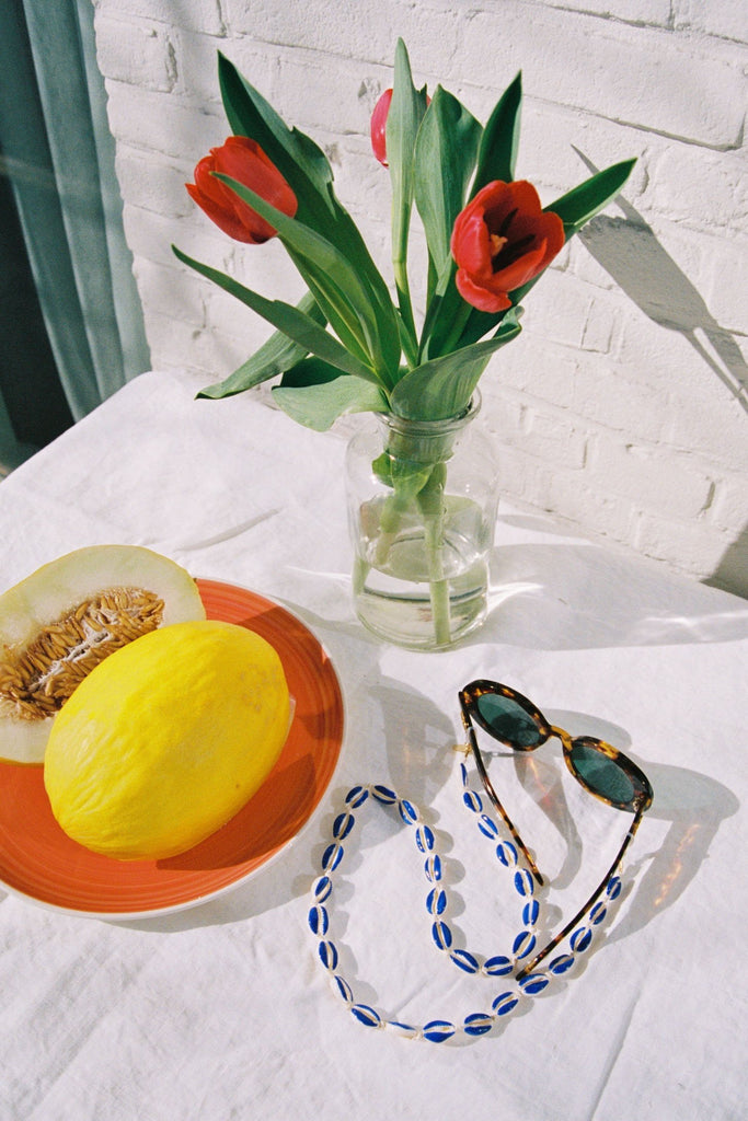 Table setting with fruits, flowers and Ocean Shell Sunnycord attached to sunglasses.