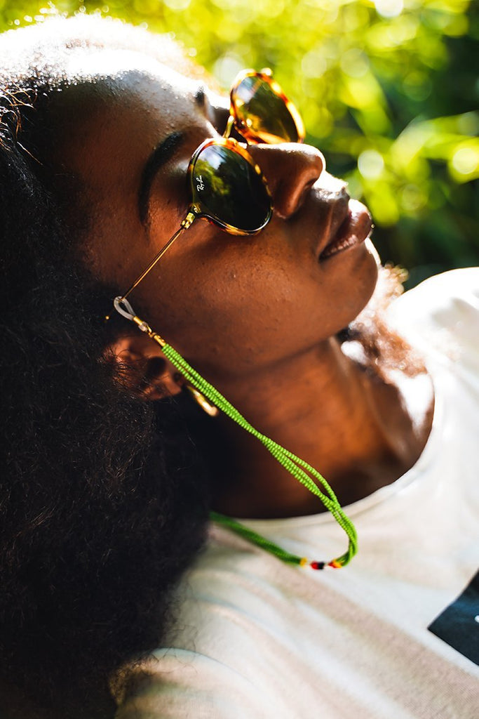 Model wearing Kijani Sunnycord, attached to her sunglasses.