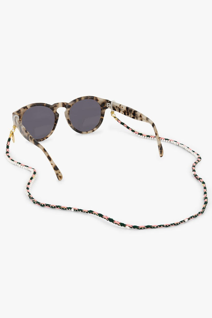 Vita Sunnycord handmade in Peru, made of green and pink woven colours and glass beads, attached to sunglasses.