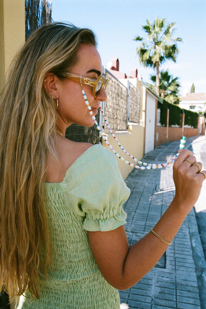 Model in green dress wearing sunglasses with Rainbow Sunnycord attached.