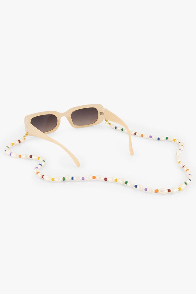 Rainbow Sunnycord made of natural freshwater pearls and rainbow beads, attached to pink sunglasses.