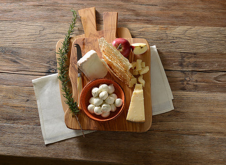wooden cheese board with a variety of cheeses