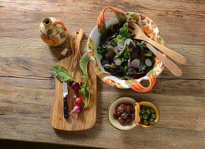 salad set with ceramic bowl, olives, wooden cutting board and olive oil