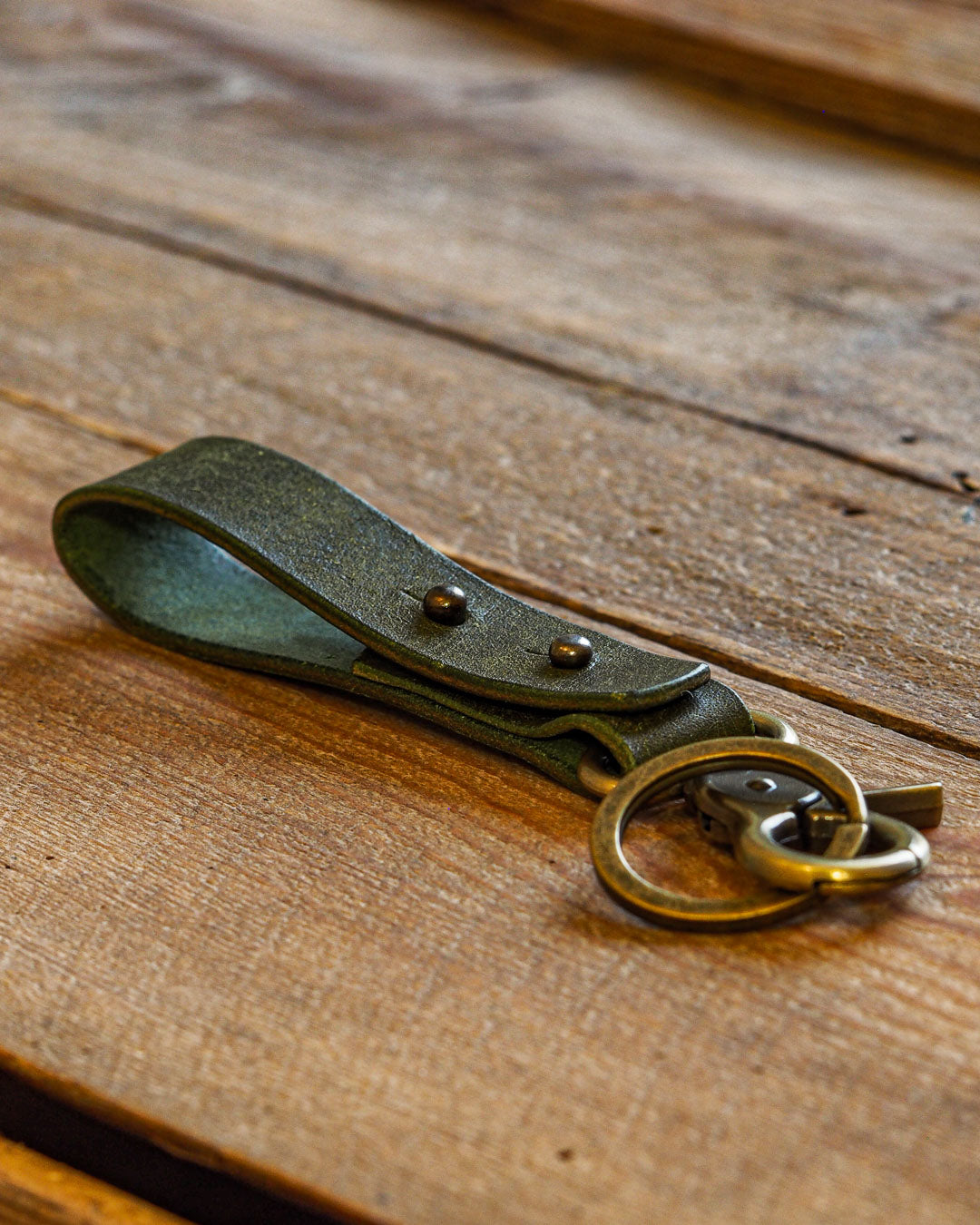 Luava handcrafted leather key fob double vegetable tanned keychain brass keyring clasp metal stud badalassi carlo pueblo leather handmade in finland olive angle