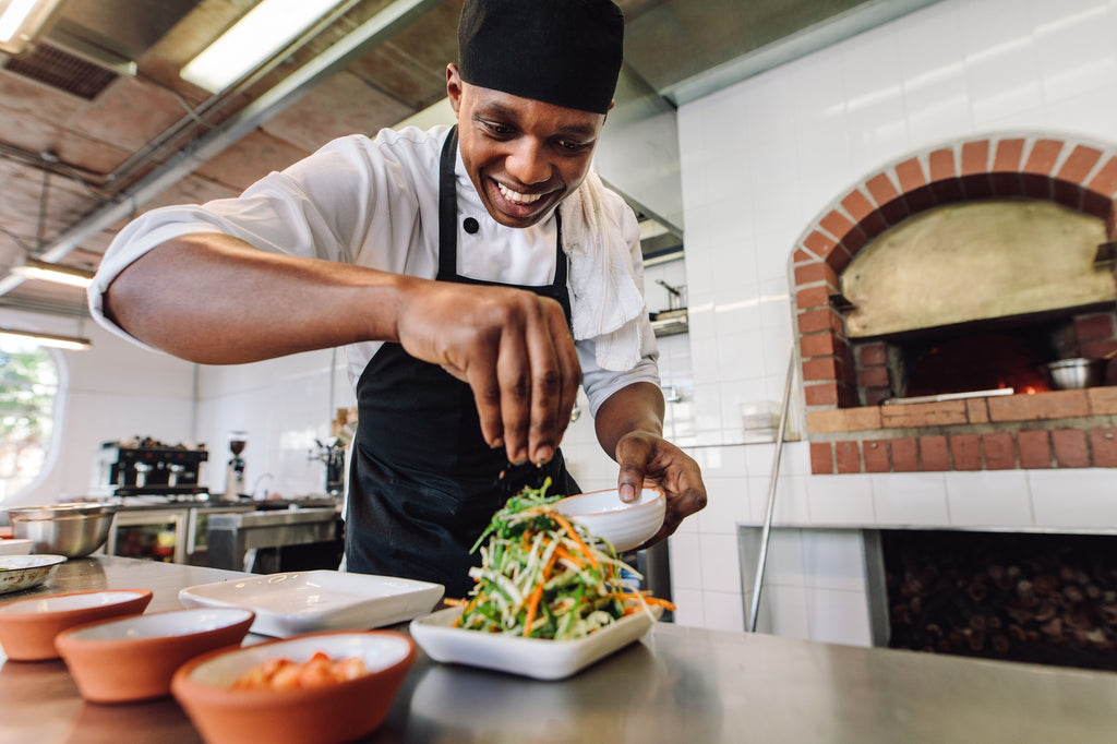 Smiling chef seasoning a salad in a kitchen.