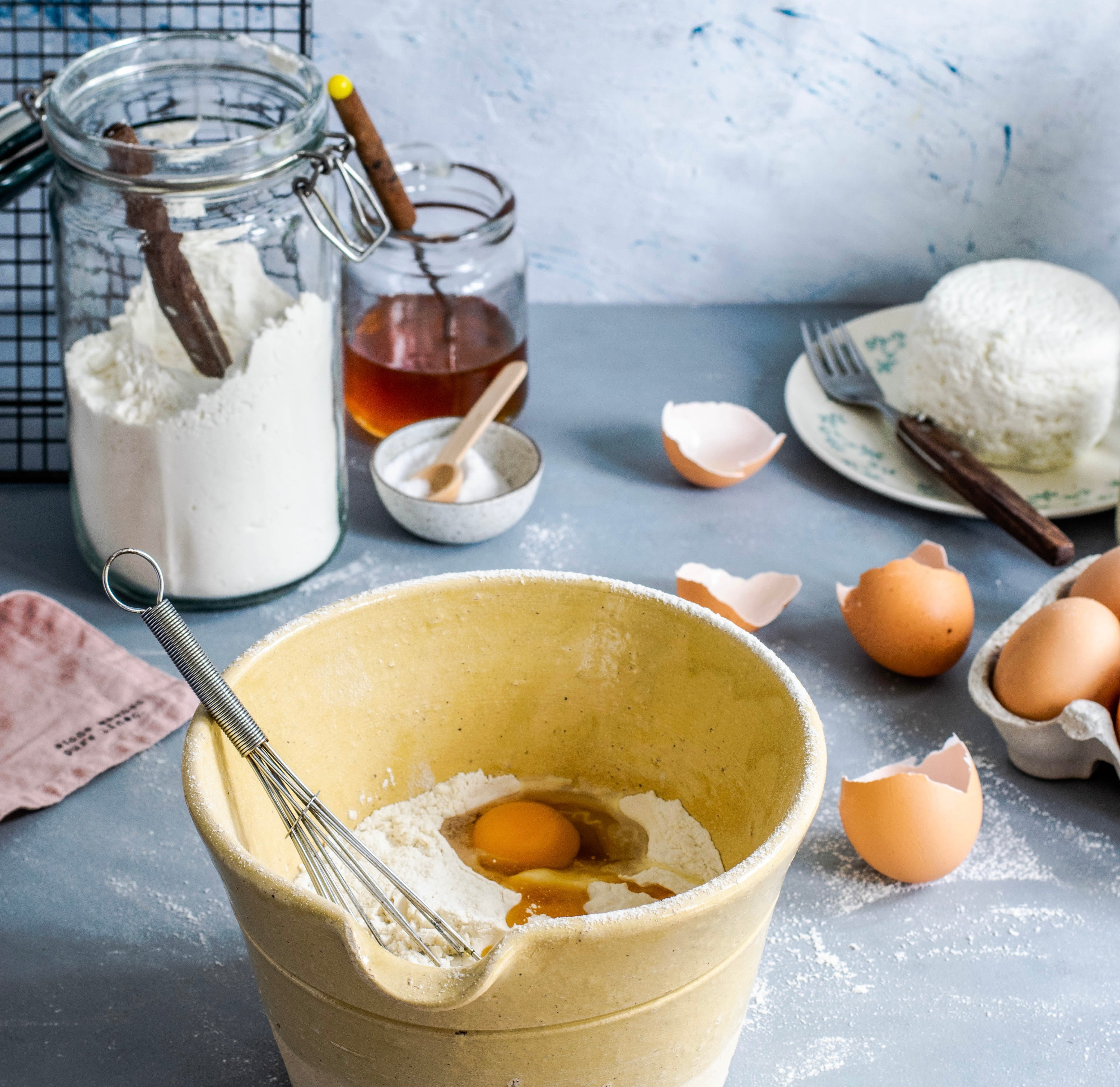 baking with honey - a rustic baking scene featuring a bowl with flour, eggs, honey, and other ingredients in unmarked jars for baking