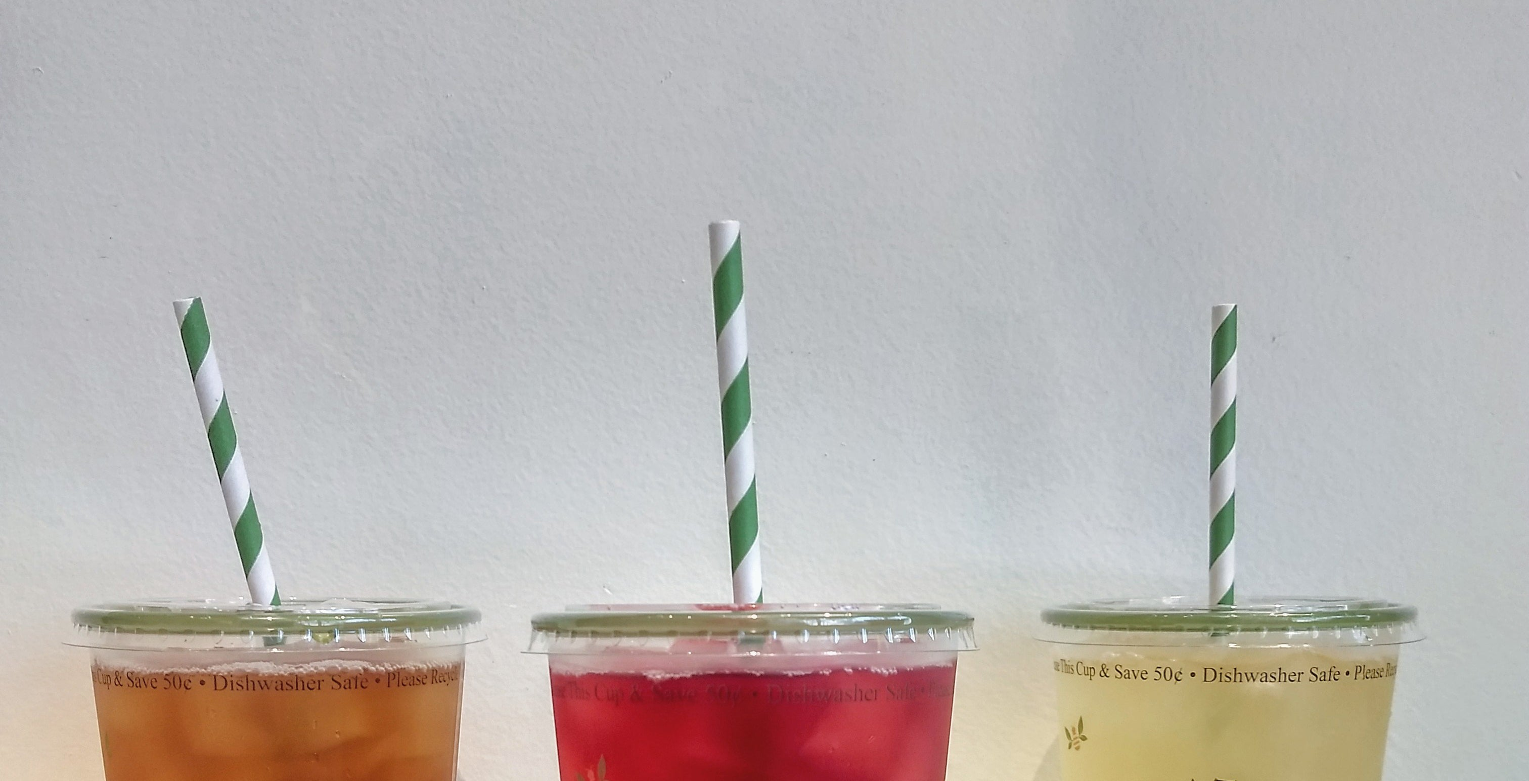 three cups of iced tea with green and white striped straws