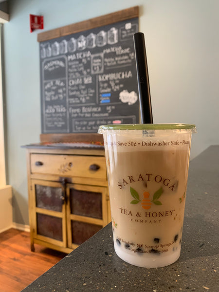 A cup of boba sits on the counter at Saratoga Tea and Honey with the chalkboard menu visible in the background