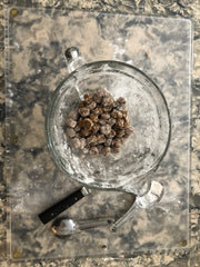 A glass bowl is full of uncooked boba pearls on a marble kitchen counter