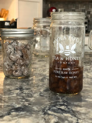 A mason jar with uncooked boba pearls sits on a marble kitchen counter next to a honey jar with cooked boba in a simple syrup