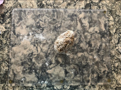 A ball of uncooked boba dough sits on a glass cutting board on a marble kitchen counter