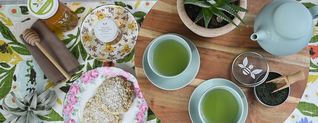 two cups of green tea served with a tea cake