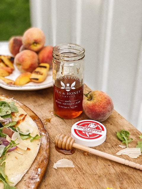 cooking with honey - pizza and grilled fruit around a honey jar