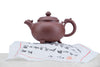 clay teapot with dragon handle, flame spout and decorated lid top/little feet resting on a teacake wrapper