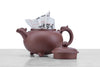 dragon teapot displayed with lid off and sitting next to teapot's dragon-shaped handle