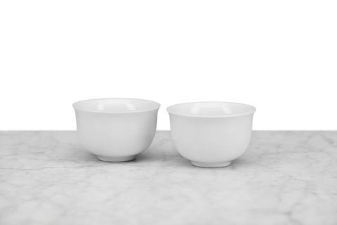 two small Japanese-style white tea cups with no handle