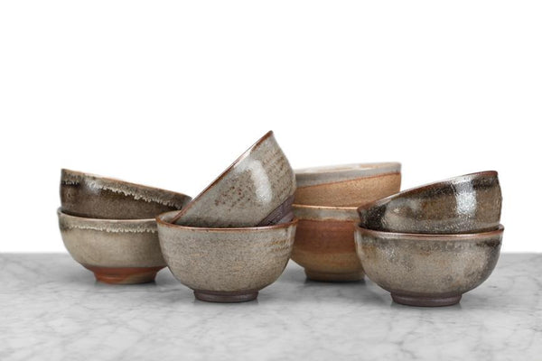 8 tea bowls stacked in four rows of two; glazes all earthy tones with variations in design and color