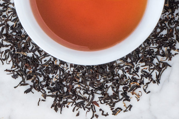 Robust Whole Assamica Black Tea Leaves Surround a Cup Of Red Tea Liquor