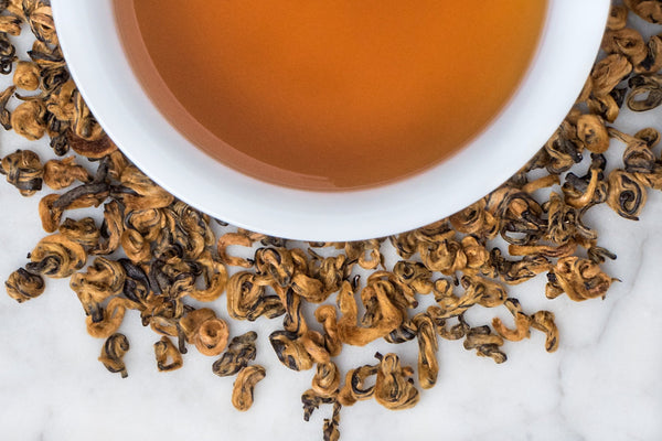 Rolled Gold Black Butterly Tea, Jin Die, Surrounding A Brewed Burnt Orange Cup