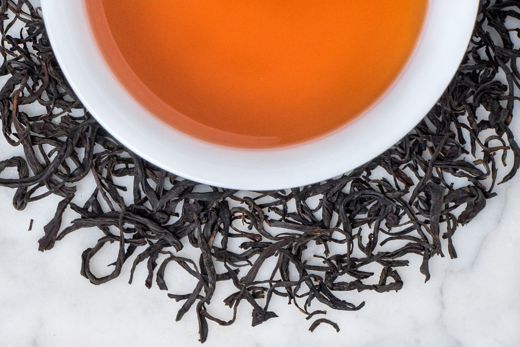 Gently Rolled Whole Black Tea Leaves Surrounding A Cocoa-y And Earthy Cup of Brewed Mao Feng
