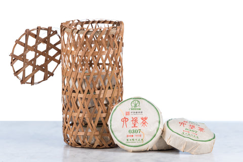 hei cha fermented aged tea cakes in a traditional basket with three tea cakes displayed on the side