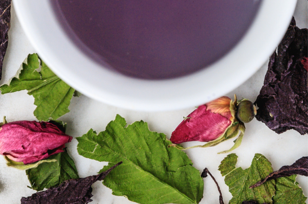 rare purple tea infusion displayed in a white cup surrounded by whole rosebuds, basil, and raspberry leaf ingredients