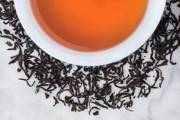 Italian Bergamot Scented Organic Black Tea Leaves Surrounding A Cup of Elegant Brewed Tea