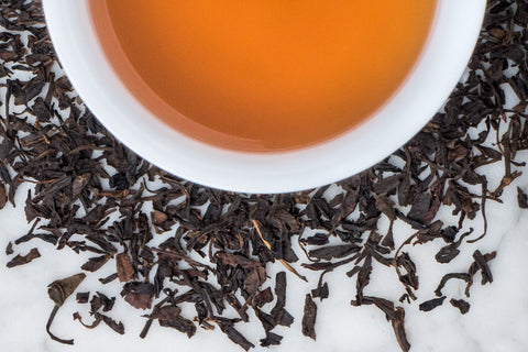 Perfectly Smoked Chinese Black Tea Leaves Surround A Cup of Brewed Lapsang Souchong