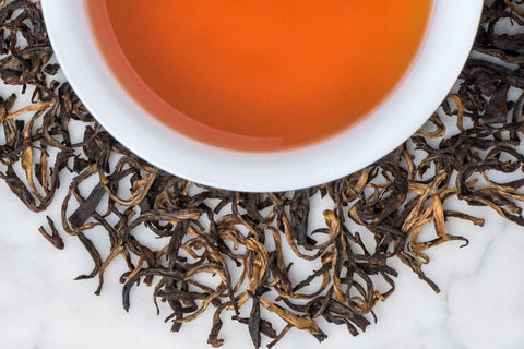 Black Leaves Twisted With Golden Buds Surround A Cup of Perfectly Steeped Yunnan Black Tea