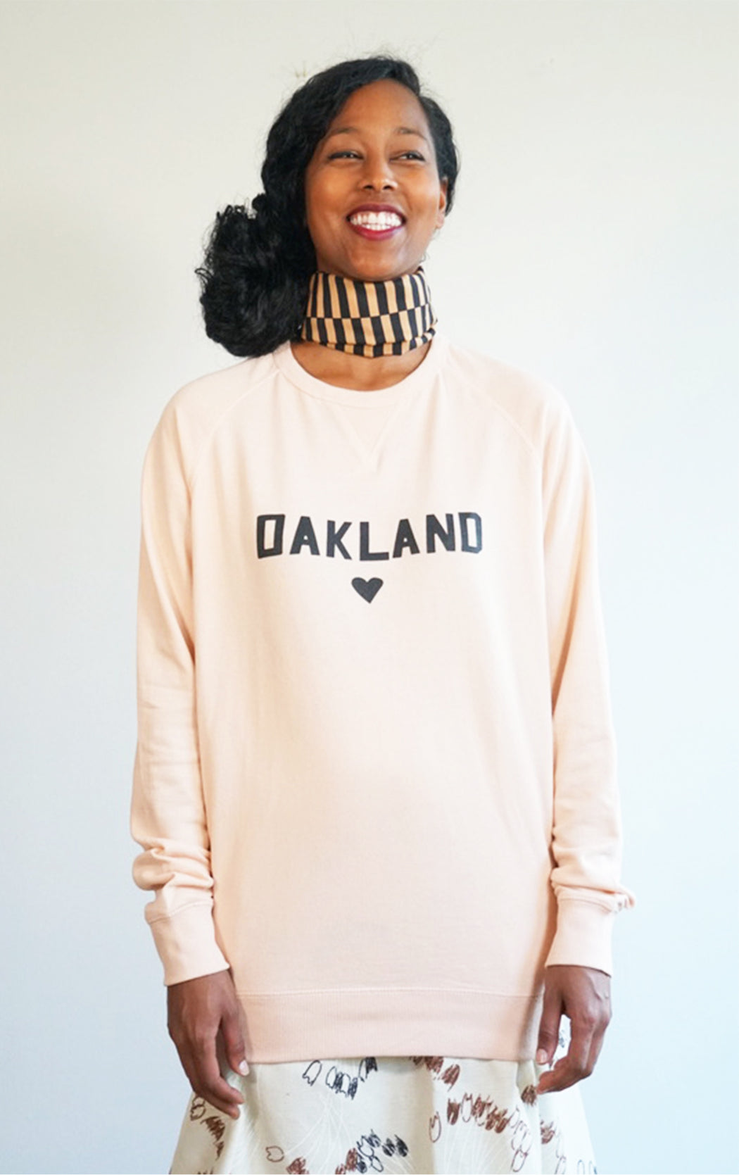 pink super soft love oakland sweatshirt in a cool crew neck style made in a soft cotton blend with love oakland heart graphic on front